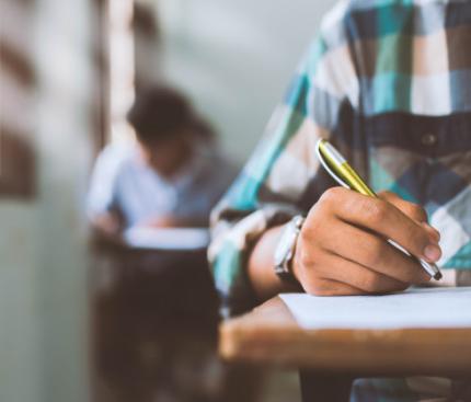close-up-alunos-escrevendo-e-lendo-exercicios-de-folhas-de-respostas-de-exame-em-sala-de-aula-da-escola-com-o-estresse_73622-858